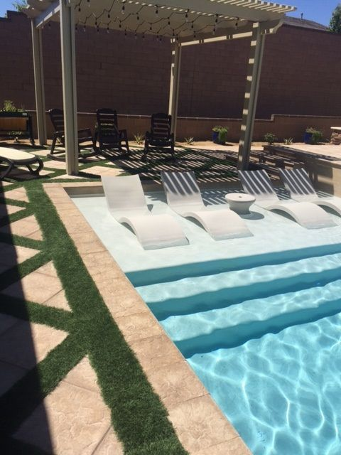 custom swimming pool with tanning ledge with loungers pergola and custom integrated grass combo decking - Custom Swimming Pool Designs