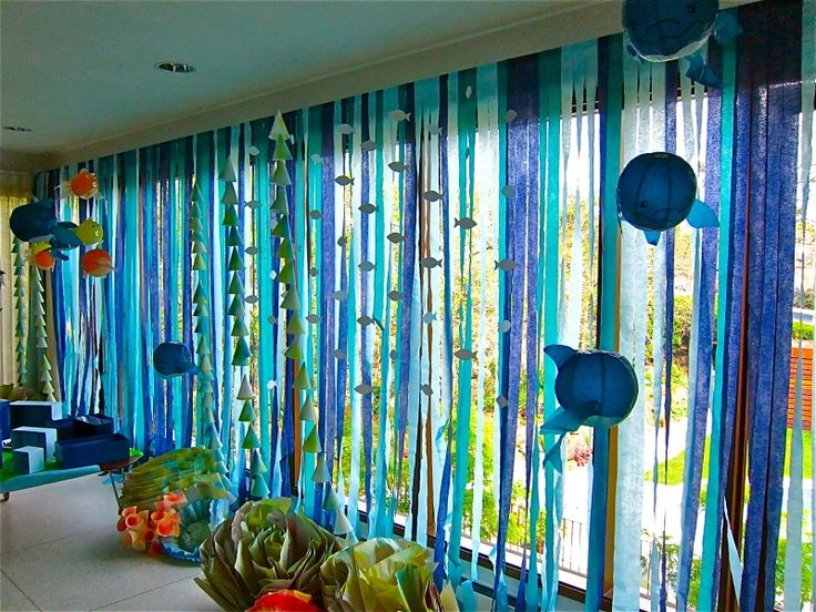 This is a picture of streamers from an ocean themed birthday party.  I wonder if I can recreate it with ribbon so it will hold up a little better.  I could also take apart my two fish mobiles and hang the fish from fishing wire using the curtain rod.  The teal curtains from IKEA would also cut down on some of the space needed to cover with ribbons. Hmmmmm...