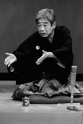 Japanese verbal entertainment, Rakugo 落語: The lone storyteller sits on a stage, using only a paper fan and a small cloth as props, and without standing up from the sitting position, the rakugo artist depicts a long and complicated comical story. The story always involves the dialogue of two or more characters, the difference between the characters depicted only through change in pitch, tone, and a slight turn of the head. (Rakugo artist, TATEKAWA Danshi in this photo)