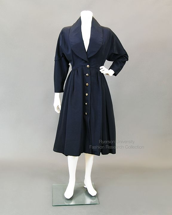 Navy blue sateen coat-dress with deep shawl collar, gathered waist, curved bodice piece forms upper part of sleeve with decorative topstitching and 6 metal buttons. Lined in rose pink silk satin. Label reads: Debutante Saks Fifth Avenue Shop. C. 1950s. FRC 1983.07.006
