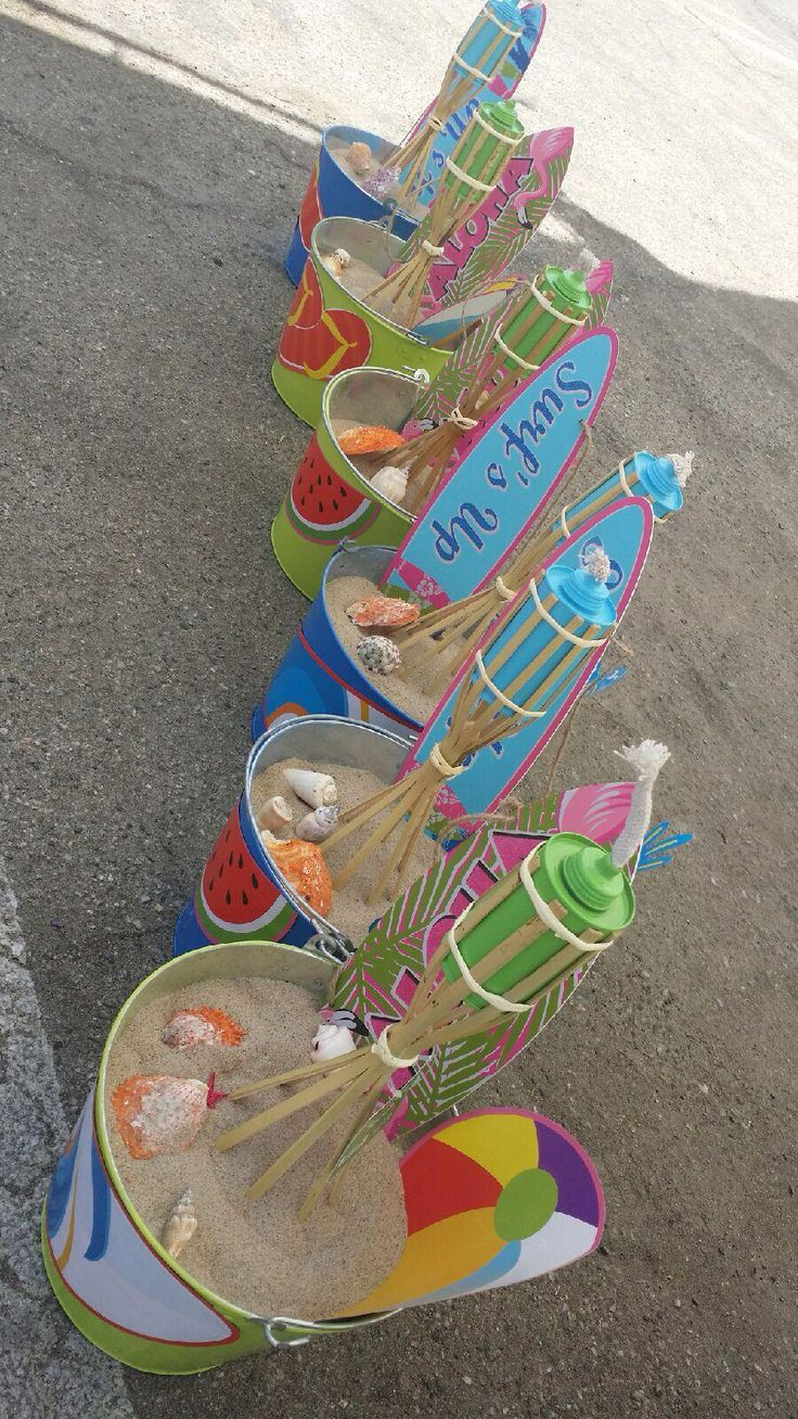 Beach Party  Centerpieces I made for my nephews Party. They were really inexpensive to make. I used beer buckets I already had , and spray painted them to my liking. Then used some surfboard/  welcome signs from the dollar store as well and tiki torches I found there too. Sand from the beach, and hot glued some fun Beach themed cutouts I found from the dollar store as well. I added another of the cut outs  to the bucket for a more colorful background. I found a package of shells downtown for…