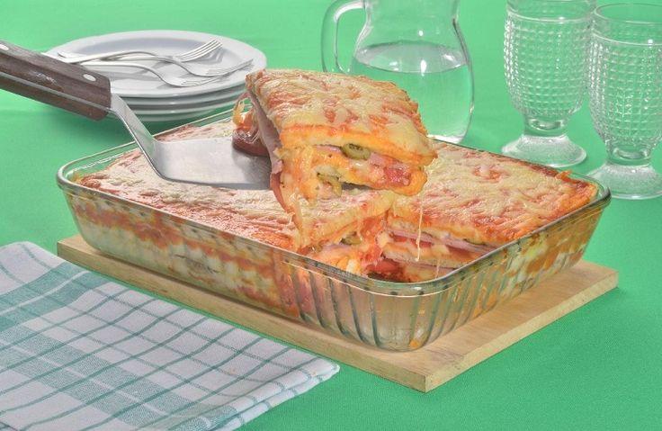 Na foto, a lasanha de pão de forma está em um refratário quadrado de vidro transparente. Uma espátula retira uma fatia da lasanha, mostrando as camadas de queijo, presunto e molho vermelho. Na decoração ao fundo, estão pratos, copos e uma jarra de vidro.