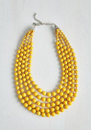 Express your signature style by accessorizing your sheath dress with this bright yellow statement necklace! Silver extras and glistening beads curl eye-catchingly around this charming accessory.