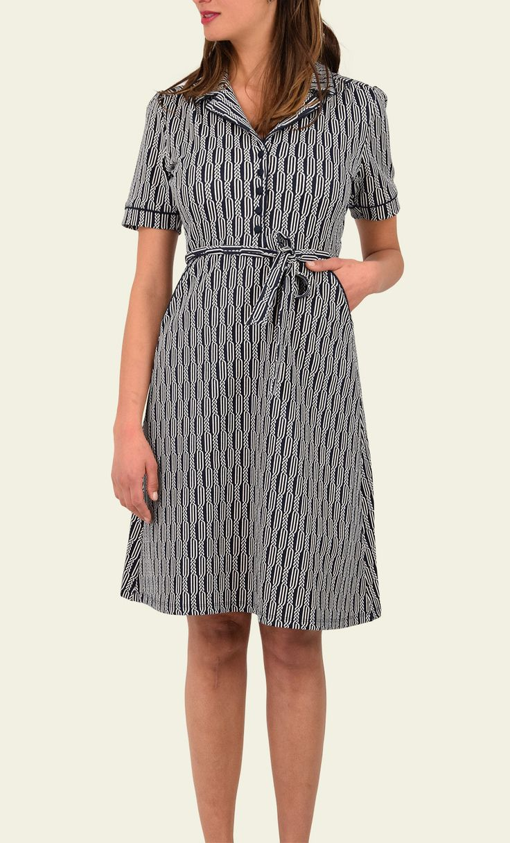 Bibi dress spiral - Een heel klassiek model met een strak lijfje en wijde rok. De revers kraag is afgezet met een effen piping, net als de korte mouwtjes en steekzakken. De stevige stof heeft een reliefje en kleedt mooi af. De jurk heeft in de taille een strik ceintuur.
