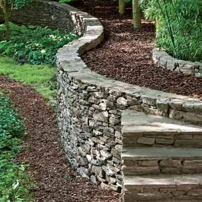 This curved mortared-stone retaining wall keeps soil in place and features steps built of the same material. New England Fieldstone, Boston Blend, about $11.60 per square foot uninstalled; The Stoneyard
