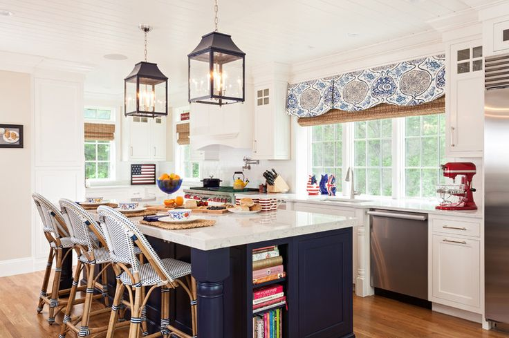 Beach Style Kitchen by Welch Company Home + Design The kitchen enjoys lots of windows and sunlight. Two large lanterns draw the eye over the island; a long valance adds pattern and more sand and navy hues.