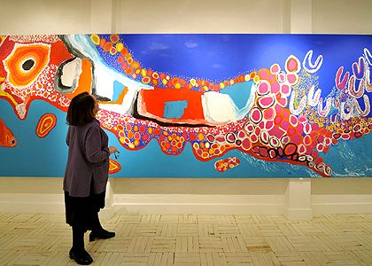 Gallery owner Beverly Knight looks at a painting by the Kaiadilt women originally of Bentinck Island.