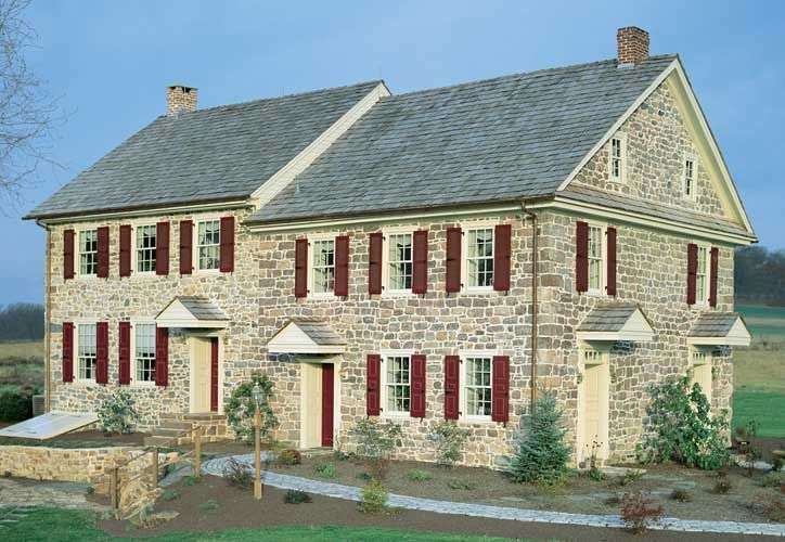 Red Paneled Shutters adorn a colonial style stone home