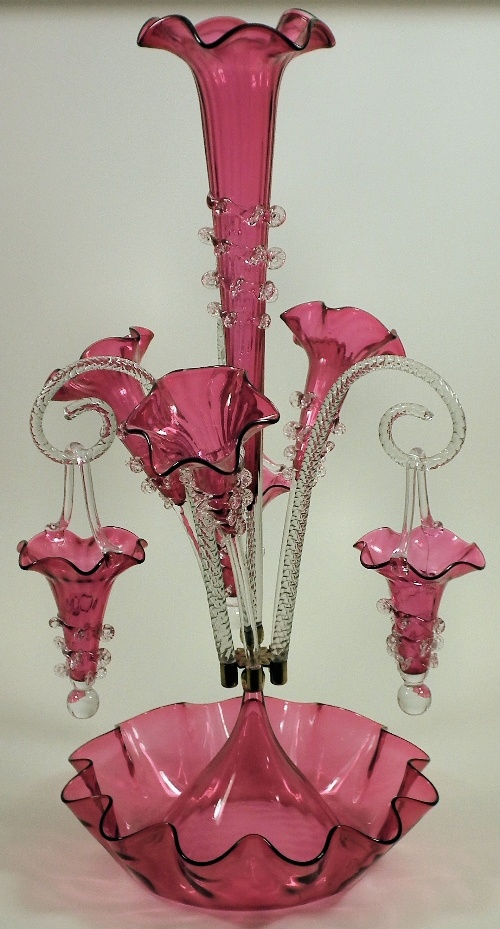 Victorian cranberry tinted glass epergne with four trumpet shaped vases and three clear glass scroll branches hung with baskets