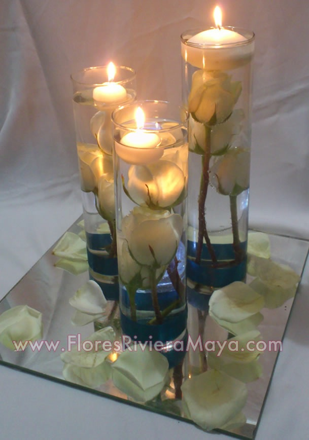 wedding centerpiece - votive in glass on a mirror with rocks and orchids in water! (no teal, royal blue for rocks & yellow flowers)