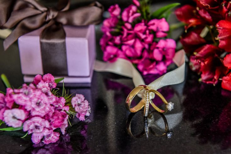 Gold and diamond wedding rings and flowers. Photographed by Anais Photography.