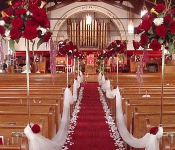 weddingbycolor.com    red aisle runner with white rose petals adorn the floor, with while tulle swags grace the pews.  Large, tall centerpieces staggered between the pews add to this dramatic church decor.