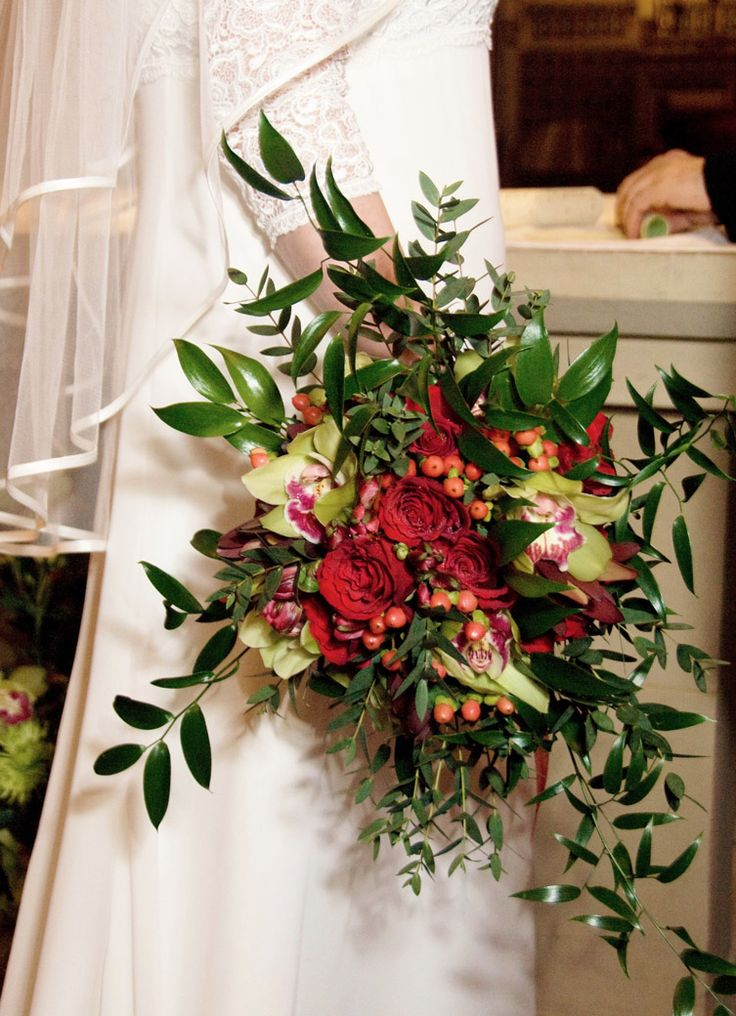"""Valentine's Day hand-tied bridal bouquet of red roses, red hypericum berries, burnt red leucadendron, green and red cymbidium orchid and lots of wild, flowing ruscus and parvi eucalyptus foliage. """"Rustic-antique"""" was the brief here! Florissimo, Shropshire. (Photo: Brian Fisher)"""