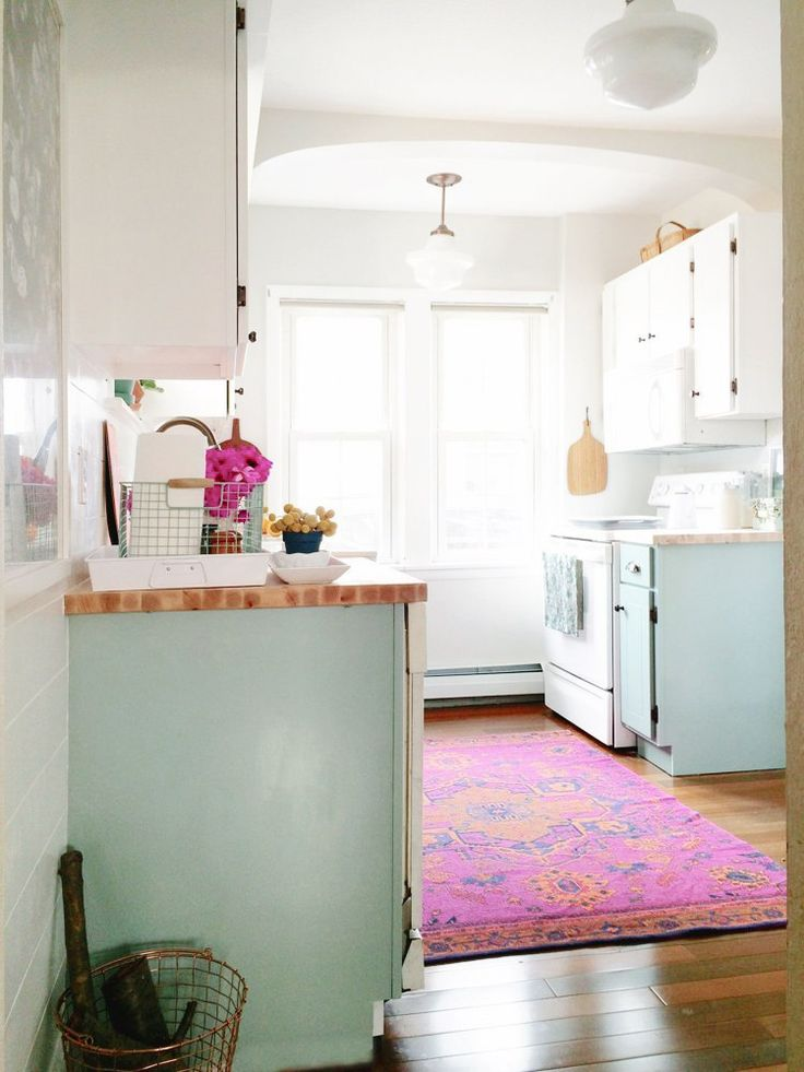Pink Persian rug and light blue cabinets in kitchen: