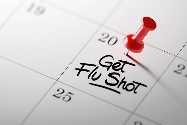 'Get Flu Shot' written on a calendar with red push pin