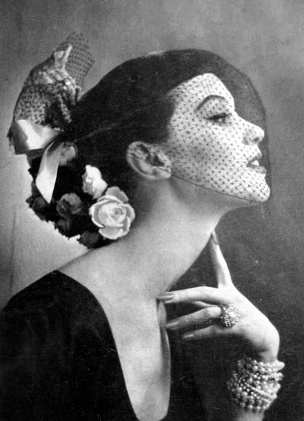 Model wearing a hat with flowers and a veil for Vogue,1951.