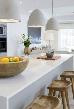 Concrete pendant lights + white kitchen + wood stools #kitchen