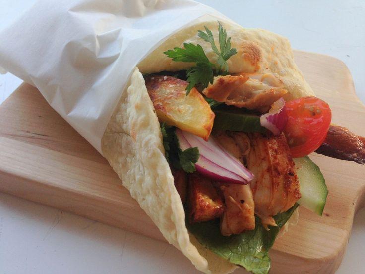 Fladbrød med pulled chicken. Hjemmelavet fladbrød med pulled chicken, grøntsager, pommes frites og dressing med bredbladet persille.