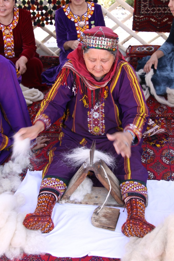 Turkmenistan May 2012 | madderlanedotcom Woman preparing spinning wool. And look at her socks!