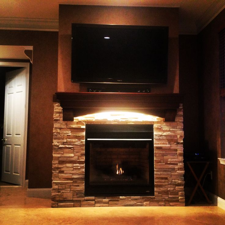 Custom fireplace. All work done by us. Cultured stone. Custom mantel with lighting. Tv mounted.