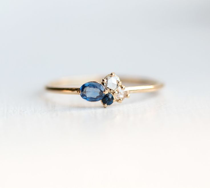 Solid 14k gold mini cluster ring with sapphire and rose cut white diamond gemstones. Handmade stacking ring by jewelry artisan Melanie Casey.