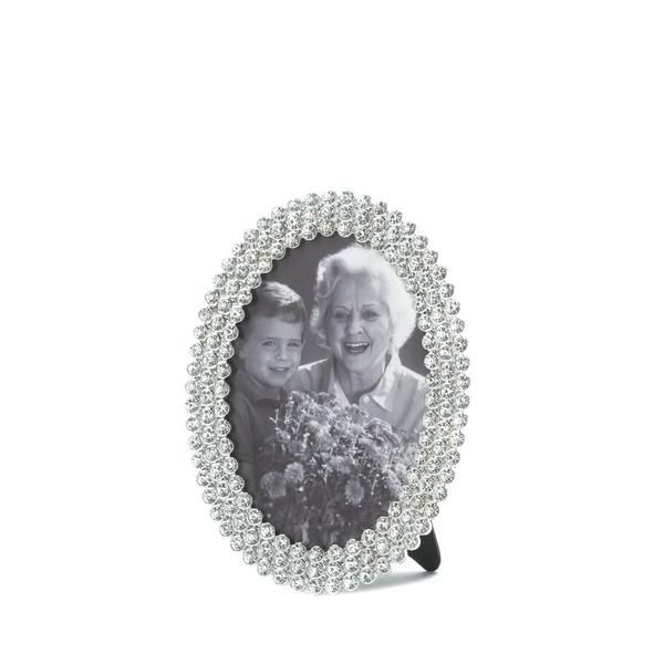 "Your sparkling photos deserve to be wrapped in sparkling jewels! This  oval photo frame features three rows of clear, glittering rhinestones  and an easel back for tabletop display.  Item weight: 0.50lbsItem dimensions:  2.50"" W x 5.50"" H x 4.50"" LMaterials: Pewter, GlassUPC: 849179021924"