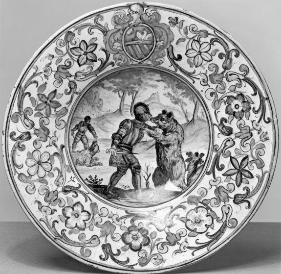 Plate with Two Knights Fighting Bears  This plate with a broad decorative border defined by floral scrolling surrounding a narrative or landscape scene is typical of the kind produced by the workshop of Carlo Antonio Gruea maiolica painter from the town of Castelliin the late 17th century. The scene in the center of two fully armored knights fighting with bears is puzzling and one wonders if the contemporary viewer found it so as well. The early 16th-century armor and the character of the…