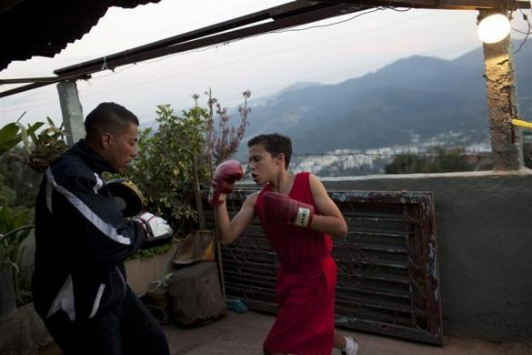 "Danilson Escalona, 13, practises Olympics-style street boxing with his coach during a training session at a gym in the low-income neighborhood of La Vega in Caracas February 10, 2011. ""Boxeo Olimpico de Calle"" (Olympic Boxing Street) is an initiative of several institutions of the Venezuelan government, which aims to keep children off gangs and drugs in an attempt to combat high crime rates in the Caribbean nation.  REUTERS/Carlos Garcia Rawlins"