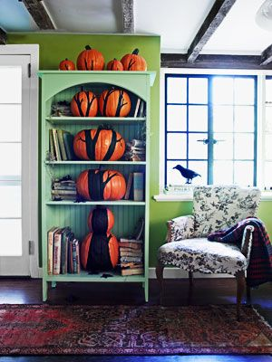 halloween decor, pumkins on a tier shelf painted with stems