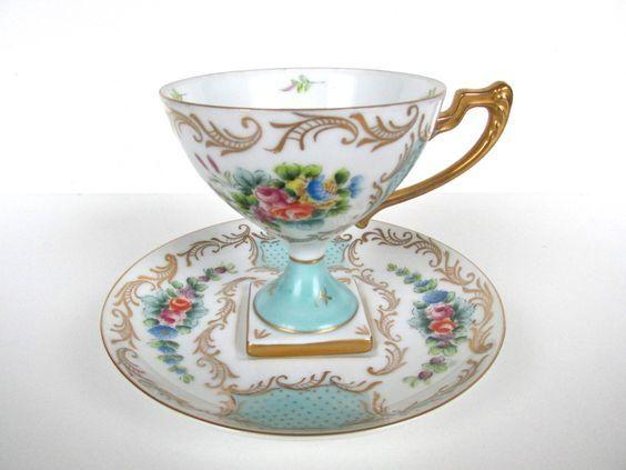 Šálek na čaj * bílý porcelán se šálkem na modrém podstavci malovaný zlatou a květinovou dekorací.