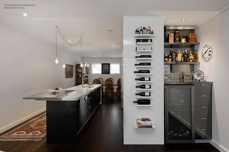 A custom designed bar and wine rack by John Perini, sits beside a stunning kitchen in this Port Melbourne home.