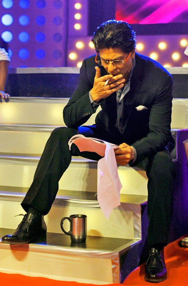 """#Bollywood star Shah Rukh Khan takes a break during an event to promote his upcoming movie """"Chennai Express"""" in Mumbai on Monday, July 29, 2013. #Fashion Warning: Smoking is Injurious to your health!"""
