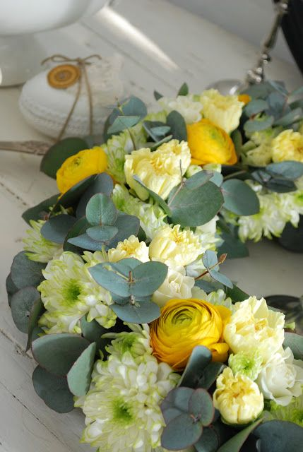 floral oasis wreath covered in eucalyptus sprigs, yellow ranunculus,, soft yellow carnation buds and white mums