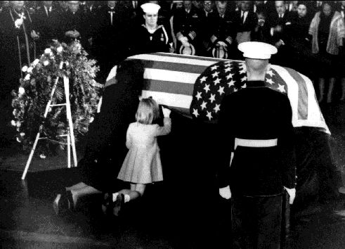 One of the more touching photos....Jackie and Caroline, in the East Room, kneeling to say a prayer. As mourners look on, Caroline slips her hand up and under the flag as if to touch her Daddy.