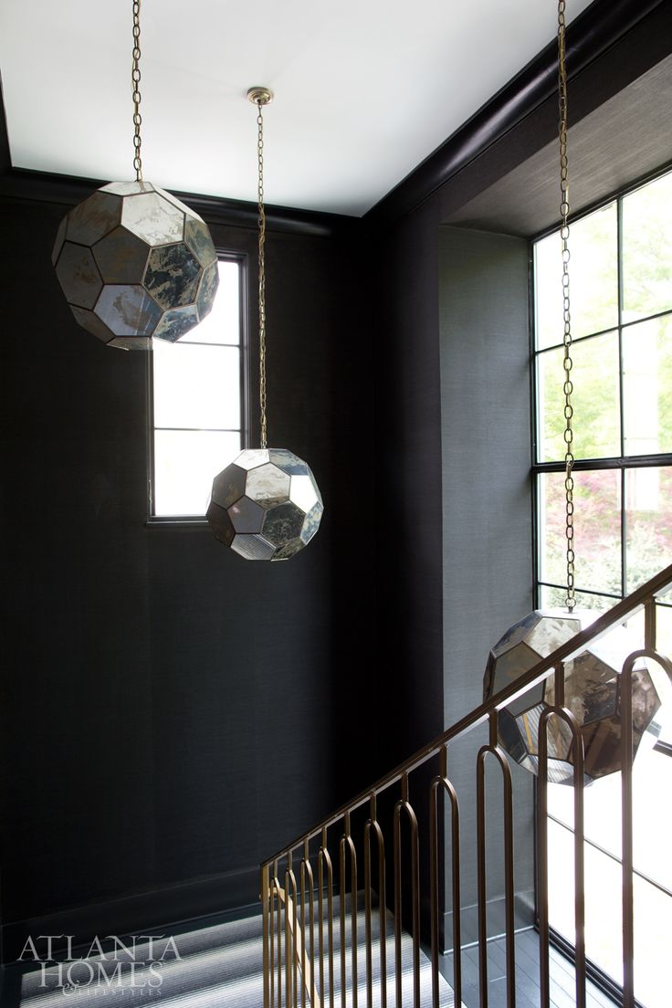 Circular glass pendants in black stairwell