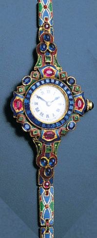 A lady's gem-set and enamel wristwatch, circa 1925. The dial with blue Roman numerals, the bezel set with well matched sapphires of Royal blue colour and very good clarity, the outer border set with pink rubies, some with scratched table facets, sapphires also with some suface scratching and emeralds, two with large chips.