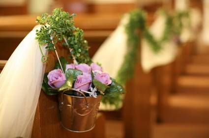 Small and simple flower arrangements at pew-ends. There are many ways to decorate pew-ends. You can have a small arrangement of flowers, arrangement in cones, small wreaths, candle arrangements or just tulle bows.