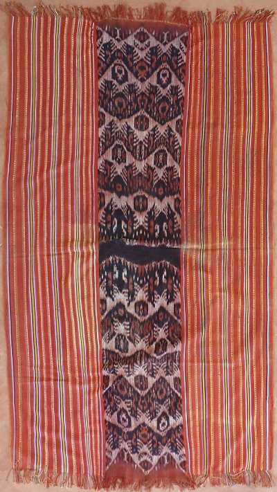 Ikat from Timor-Barat, Timor, Indonesia: Typical mau (man's cloth) from Amanuban. Central band of ikat done in hand spun yarn and natural dyes with four rows of birds that alternately touch wings or feet, executed in morinda red and belapit (morinda overdyed with indigo).