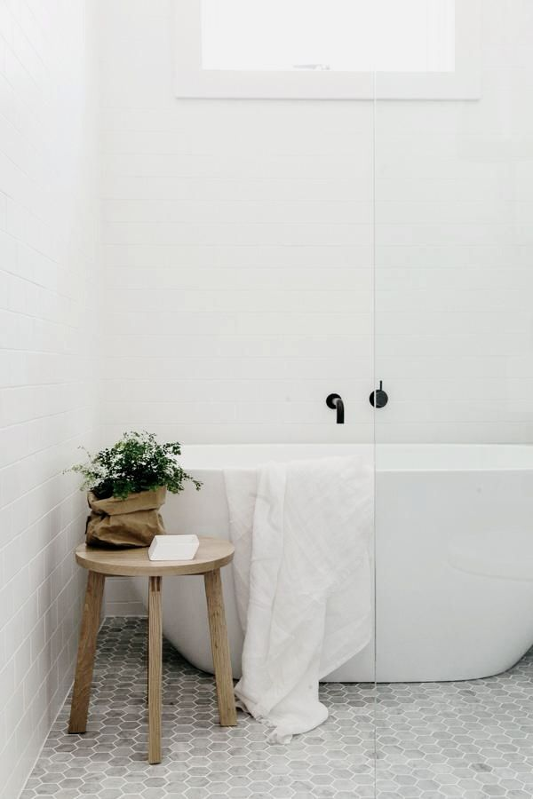 Grey hexagon marble tiles. Modern free standing tub. White subway tile.