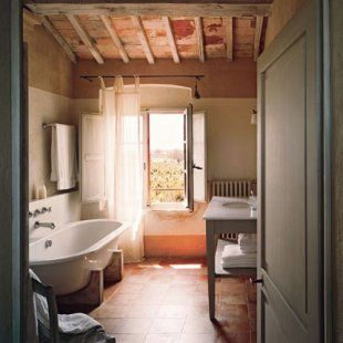 Salle de bain toscane avec baignoire posée sur sabots en bois et dalles roses pâles