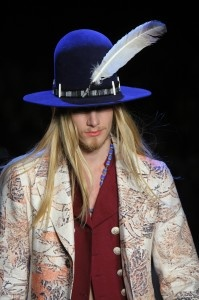 Represented above is how decoration can be influential to fashion. Decoration may include things such as accessories, shoes, handbags, etc. This model is wearing a hat with a feather in order to express decoration through his style/choice of fashion.
