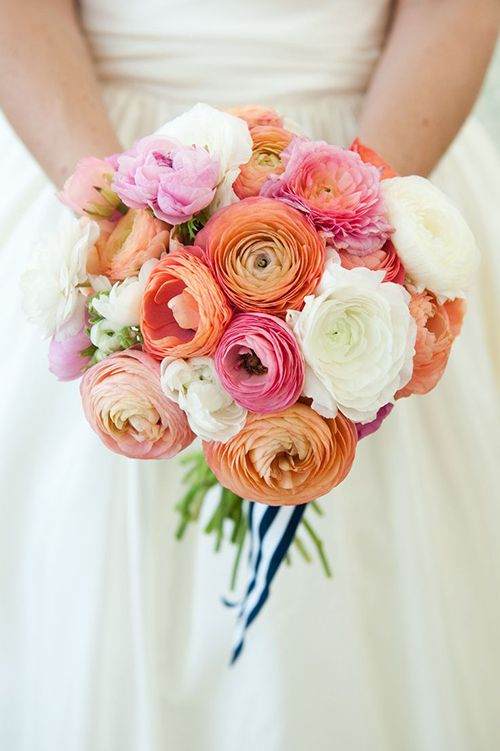 A multicolored ranunculus wedding bouquet tied with a striped ribbon | Brides.com