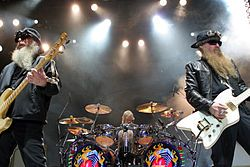 ZZ Top -ZZ Top is an American rock band from Houston, Texas. Formed in 1969, the group consists of Billy Gibbons (guitar and vocals), Dusty Hill (bass and vocals), and Frank Beard (percussion).