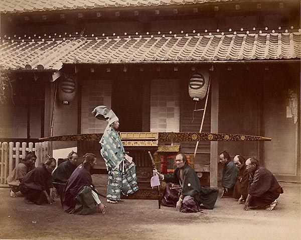 A Nobleman and His Retinue. Tinted albumen print, 1875-1878. The scene shows a slice of daily life in Meiji-era Japan: the gentleman in blue is stepping into the kago (a palanquin or sedan chair.) The three men kneeling at the left and right of the photograph will carry the sedan chair (with the passenger inside) by placing the long horizontal bar on their shoulders. The two samurai with swords may be a bodyguard and a chancellor.