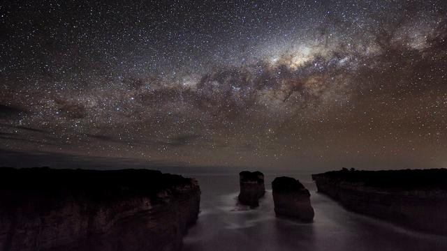 Clouds and the Milky Way captured in motion over the coastline of