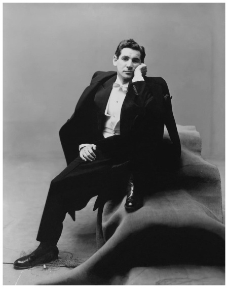 Leonard Bernstein, conductor and composer, wearing a tuxedo, sitting on a group of carpeted boxes Condé Nast photo by Irving Penn, from the Book Nostalgia in Vogue New York, March 19, 1947