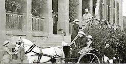 Die Aufnahme zeigt die Großherzogliche Familie um 1880 auf ihrem Schloss Wolfsgarten bei Darmstadt. Auf der Treppe stehen Großherzog Ludwig IV. und seine Frau Alice, vor dem Pferd ihre Tochter Victoria, auf dem Einspänner Elisabeth und Alix und auf dem dreirädigen Fahrzeug Ernst Ludwig, der spätere Großherzog.