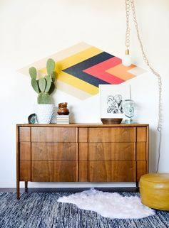 Lovely sideboard with geometric pattern above, complete with cosy sheepskin rug!