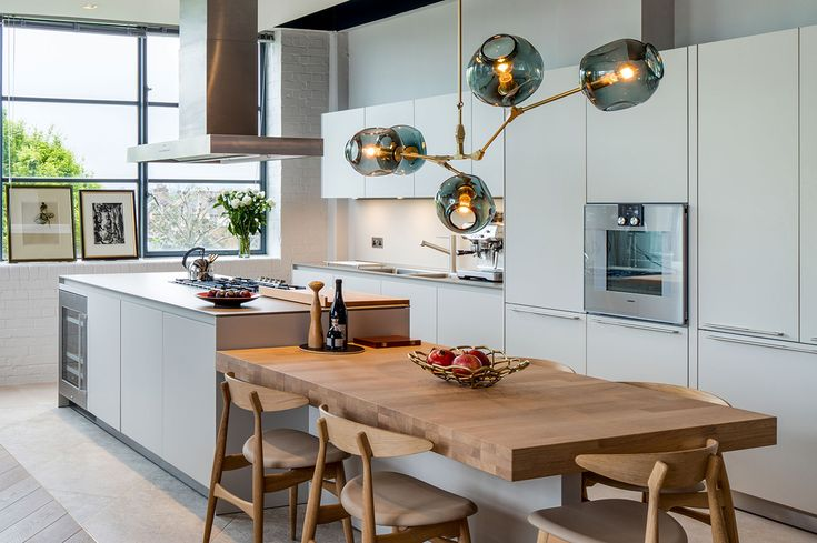White gloss kitchen and natural wood dining table with brass feature lighting - The Rovers Return Luxury interior designs by Daniel Hopwood and Studio Hopwood. Designs featuring on the Martyn White Designs Blog