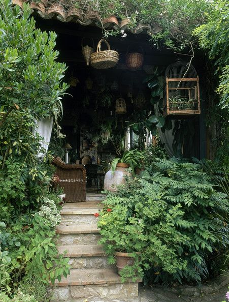 Adore this shady space with all the hanging elements -- birdcages, baskets, etc. -- surrounded by plants.